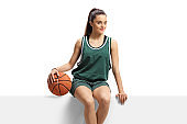 Female basketball player sitting on a panel and holding a ball