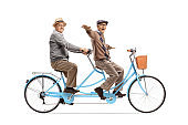 Cheerful elderly men on a tandem bicycle