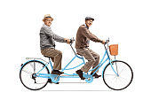 Two elderly men riding a blue tandem bicycle and smiling at camera