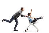 Father pushing son inside a shopping cart