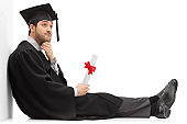 Pensive graduate male student holding a diploma sitting on the floor and leaning on a wall