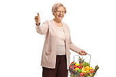 Elderly lady with fruits and vegetables in a shopping basket showing thumbs up