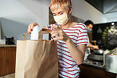 Female fast food worker with protective face mask packing meals for delivery