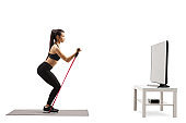 Young exercising with a resistance band and watching tv