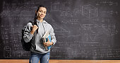 Girl with backpack and books standing in front of a blackboard written with math formulas