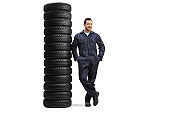 Full length portrait of an auto mechanic worker leaning on a pile of many car tires