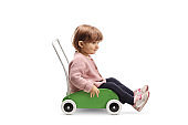 Little girl sitting inside a wooden toy cart and smiling