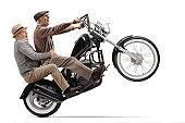 Crazy senior men riding a motorbike on one wheel