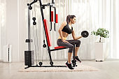 Young female exercising with a dumbbell and sitting on a fitness machine at home
