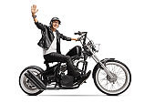 Elderly biker in leather jacket riding a chopper and waving