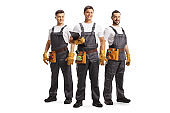 Full length portrait of a team of service workers with tool belts isolated on white background