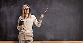 Female teacher standing in front of a blackboard and pointing with a stick