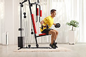 Young man exercising with barbells on a fitness machine at home