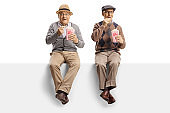 Elderly men sitting on a panel eating popcorn and smiling at camera
