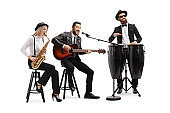 Man playing an acoustic guitar, female sax player and a man conga drummer performing in a band