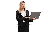 Young blond businesswoman standing and working on a laptop computer