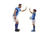 Adult football player gesturing high five with a junior football player
