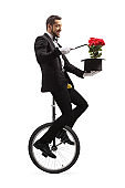 Magician performing on a unicycle with a magic wand, hat and red roses