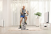 Cheerful elderly man in sportswear riding a stationary bike  at home