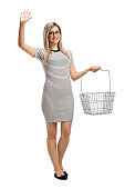 Young blond female posing with a shopping basket and waving