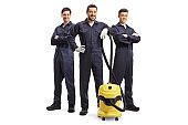 Full length portrait of male cleaners with a vacuum cleaner