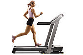 Fit muscular woman running on a treadmill