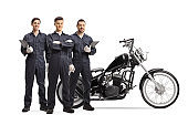 Team of mechanics standing with a customized chopper motorbike