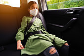 Young girl driving on the back seat of a car during COVID-19