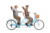 Cheerful elderly men riding a tandem bicycle and spreading arms