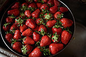 Juicy ripe red strawberries are washed in a steel bowl full of water.