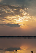 Sunset with clouds on the sky reflected on water