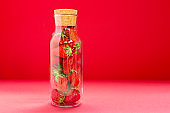 Bright juicy selected strawberries in a glass bottle.