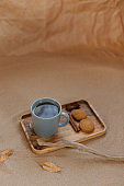 A mug of tea on a wooden tray, next to homemade cookies and spices. Background of sand and craft paper.