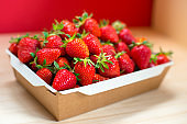 Bright juicy selected strawberries in a portioned cardboard box.