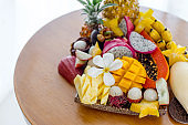 Juicy ripe tropical Thai fruits on a wooden dish.