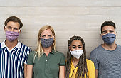 Friends wearing face protective mask to avoid corona virus spread - Young millennial people portrait during coronavirus outbreak - Health care people and youth multiracial lifestyle friendship concept