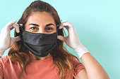 Mature Latin woman portrait wearing protective face mask and gloves - People self quarantine for preventing and stop corona virus spread - Healthcare and coronavirus confinement concept