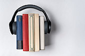 Headphones worn on a stack of bookson a white background. Literature in audio format. Audiobook concept