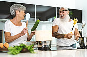 Happy senior couple having fun cooking together at home - Elderly people preparing lunch in modern kitchen - Retired lifestyle family time and food nutrition concept