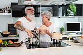 Happy senior couple having fun cooking together at home - Elderly people preparing health lunch in modern kitchen - Retired lifestyle family time and food nutrition concept