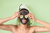 Happy smiling girl applying facial carbon mask portrait - Young woman having skin care cleanser spa day - Healthy beauty clean treatment and and self care lifestyle concept - Green background