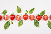 Top above overhead view photo of a row of tomatoes and spinach isolated on white background