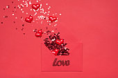 Happy St Valentines day concept. Top above overhead close up view photo of unwrapped envelope and flying away shiny stylish glitter in shape of hearts on monochrome red bright background