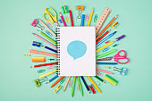 Idea sharing concept. Top above overhead view photo of colorful stationery and blank notebook with blue bubble on top isolated on turquoise background