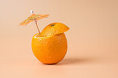 Fresh beverage concept. Close-up photo of cut orange with a cocktail umbrella in it isolated on sandy background