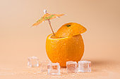 Summertime concept. Close-up photo of cut orange with a cocktail umbrella in it and ice cubes isolated on sandy background