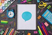 Expressing opinion concept. Top above overhead view photo of colorful pens and pencils around blank notebook with blue bubble sticker isolated on blackboard