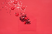 Romantic feelings expression concept. Flatlay photo of unwrapped paper envelope and flying away shiny shimmer glitter and hearts on bright color background