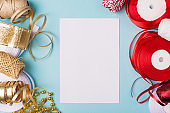 Steps how to wrap giftboxes, List what to buy concept. Top above overhead close up photo of tape ribbon accessories with white empty blank page on blue desk table