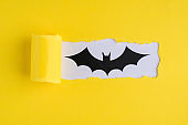 Halloween concept. Top above overhead view close-up photo of torn yellow paper and bat over white background with copyspace